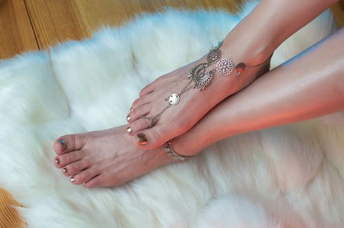 From above crop unrecognizable pedicured female legs in silver anklets on fluffy white carpet
