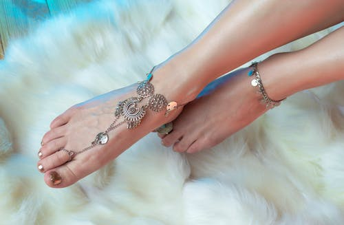 High angle anonymous female legs with stylish pedicure wearing oriental silver anklets above fluffy carpet