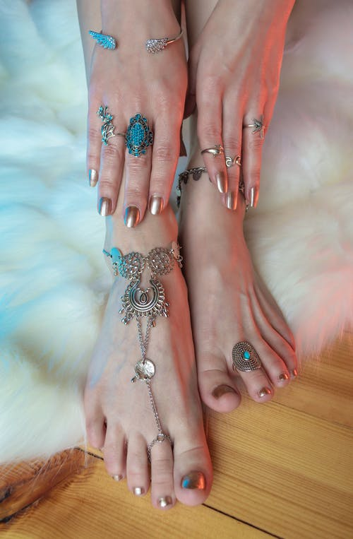 Crop anonymous female with manicured hands in rings touching legs in silver anklets above white carpet