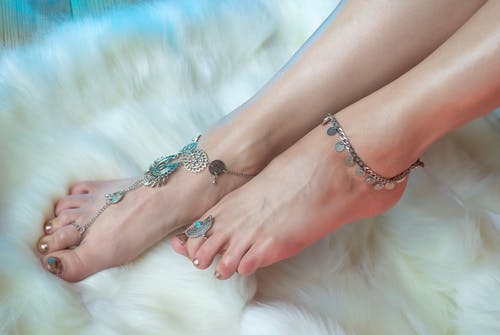 Crop anonymous female legs with stylish pedicure wearing silver anklets and rings in oriental style above white fluffy carpet