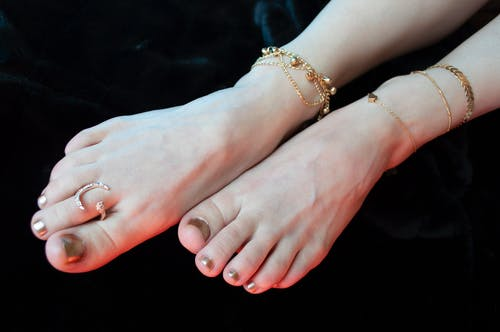 Crop anonymous female legs with stylish pedicure wearing golden anklets and ring on black background