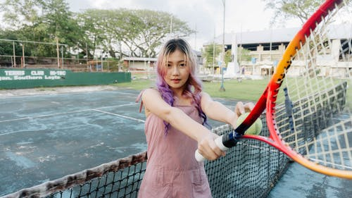 A Girl Holding a Tennis Racket and Ball
