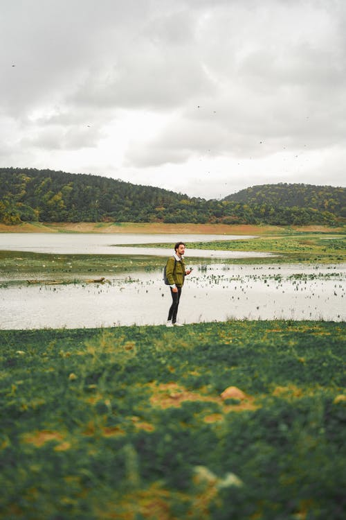 Man on grassy coast near pond and hills