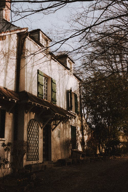Facade of old fashioned house with shutters on windows and canopy located near tall trees in suburb terrain of countryside