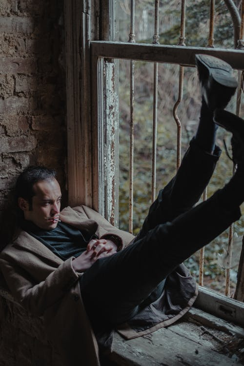 Sad man in elegant wear on windowsill of neglected house