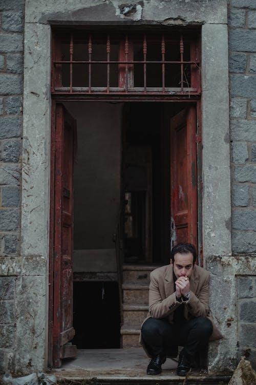 Bankrupt man sitting at entrance of damaged building