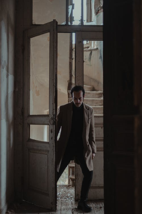 Full body of disappointed male in elegant wear entering in abandoned damaged house