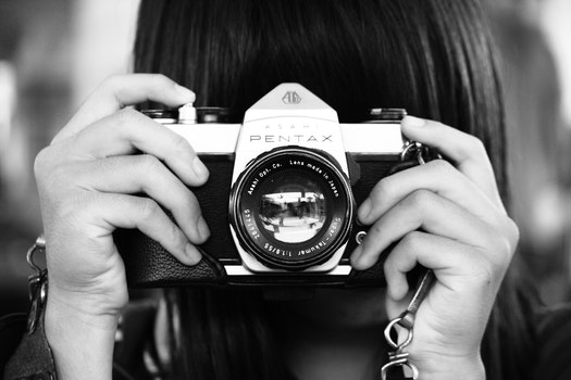 Woman Holding Dslr Camera in Grayscale Photography
