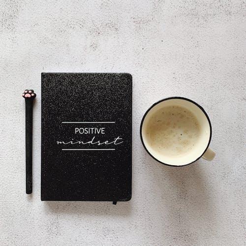 Black Book Beside White Ceramic Mug