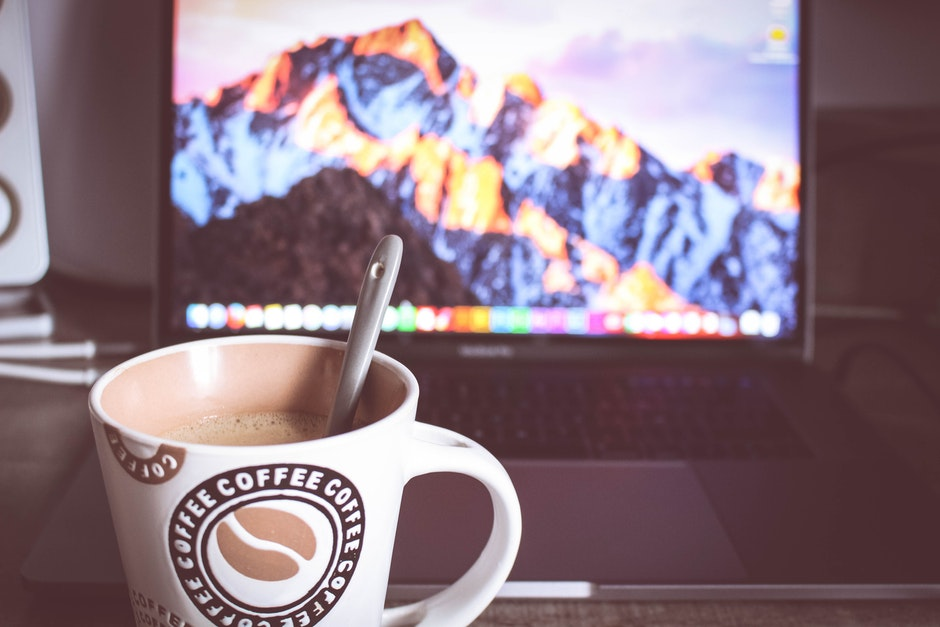 Photo of Cup of Coffee in Front of the Laptop