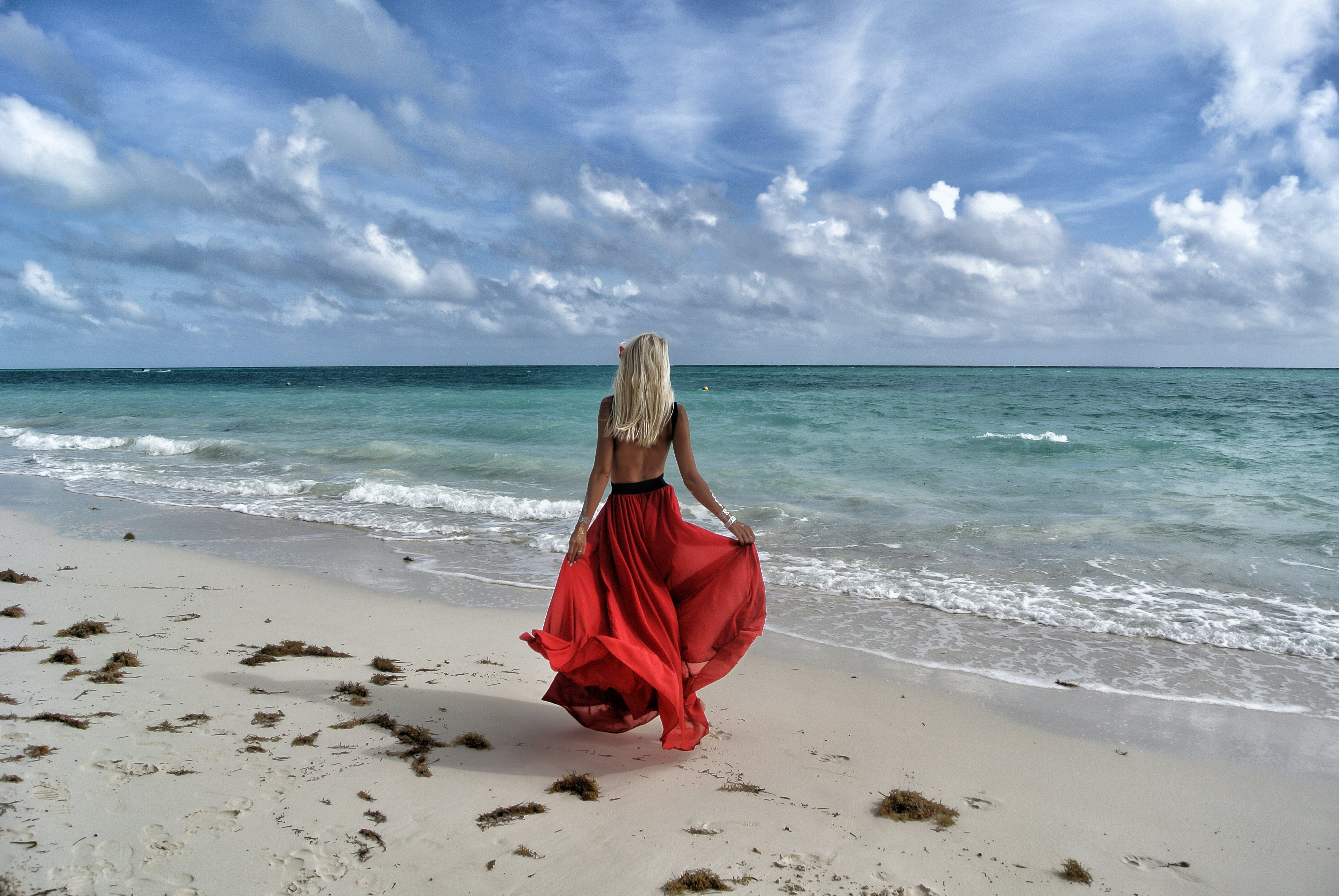 Woman Wearing Red Dress Walking on Seashore Under Blue and White Sky