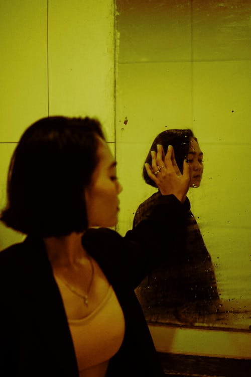 Side view of young depressed ethnic female in jacket reflecting in mirror with water drops while looking away indoors