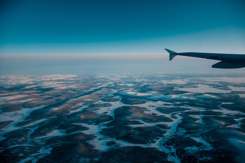 Wing of airplane flying in blue cloudless sky with skyline above vast terrain covered with snow in nature on winter day