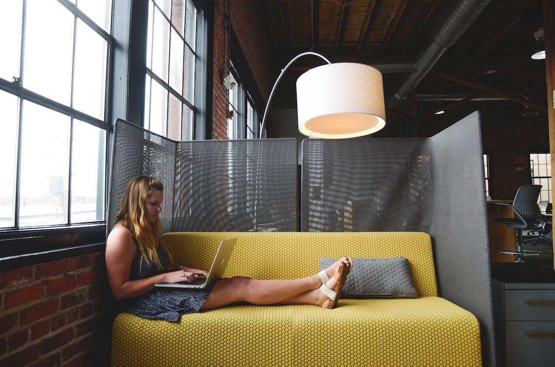 Woman Typing on Laptop Sitting on Sofa