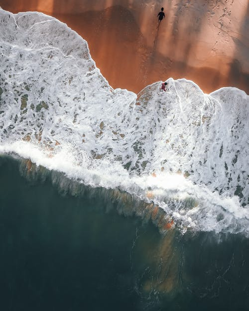 Drone view of travelers on sandy beach of powerful blue ocean with foamy waves in tropics
