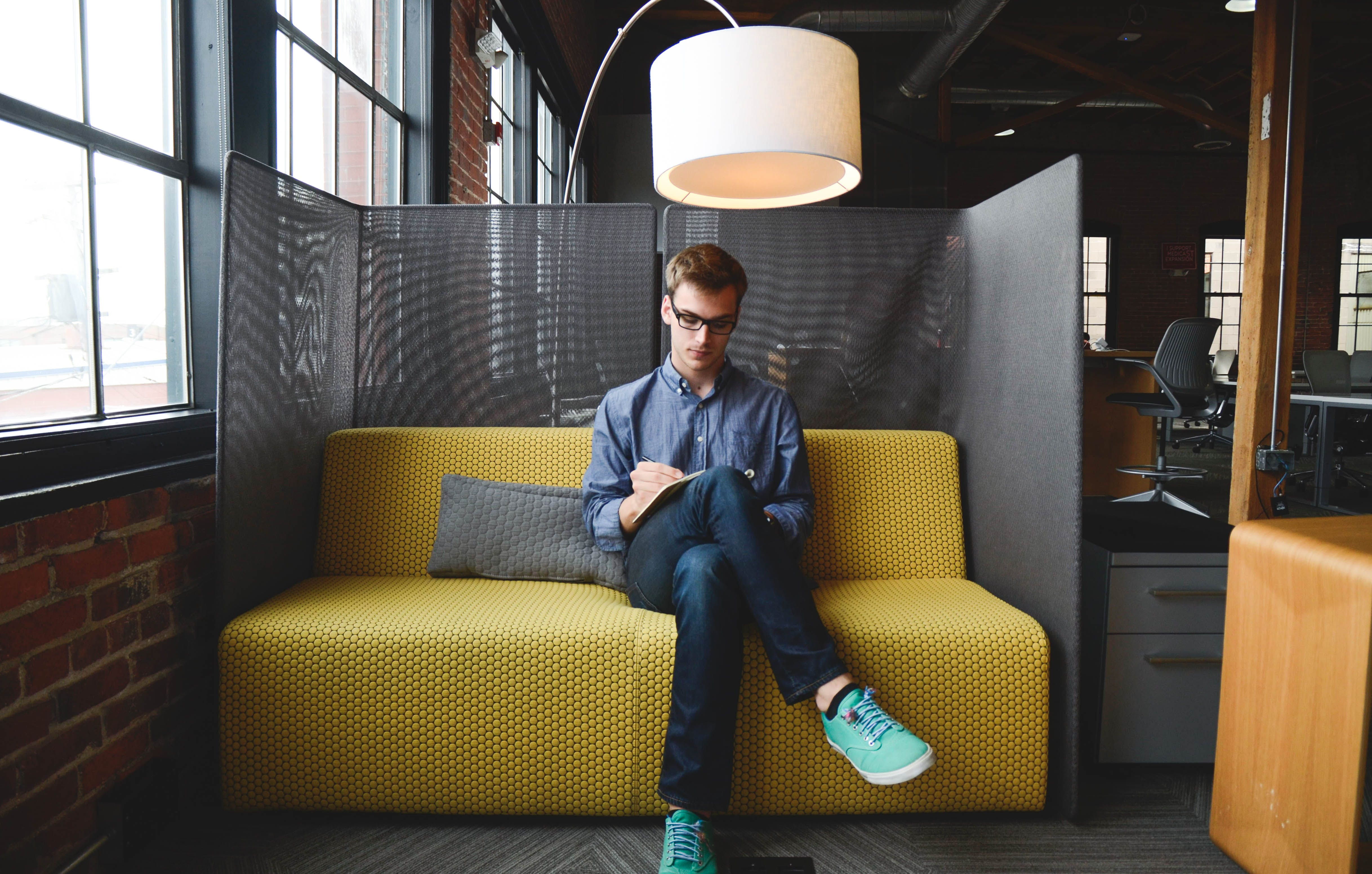 Man Wearing Blue Dress Shirt Sitting on Yellow Sofa