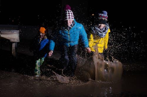 aile, çocuklar, sıçrama, su birikintisi içeren Ücretsiz stok fotoğraf