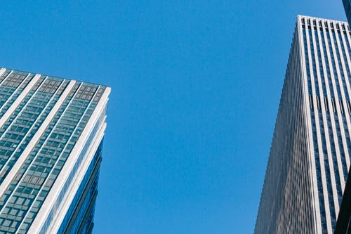 From below of modern business centers under bright blue cloudless sky in daytime