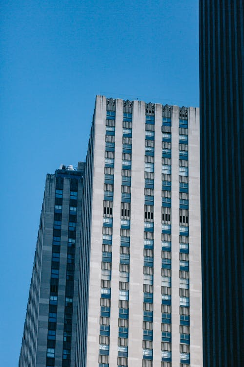 Tall gray modern building on avenue under cloudless sky
