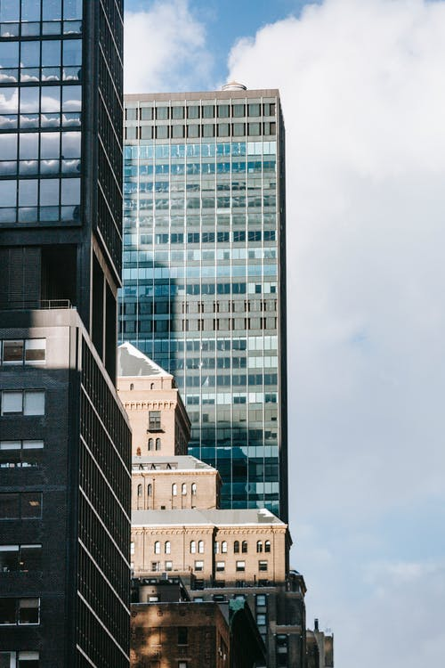 Tall shiny glass buildings on urban street in daylight