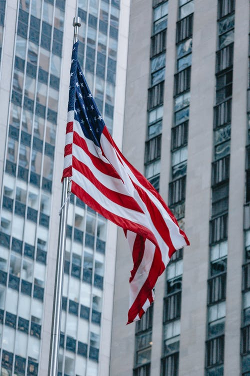 From below national US flag waving on pole against modern skyscraper in urban city district