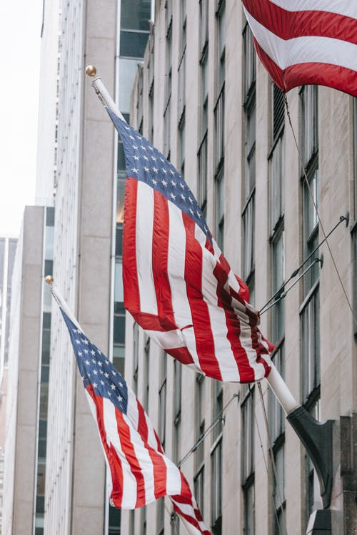 Row of American flags with stripe and star ornament on wall of embassy building in town