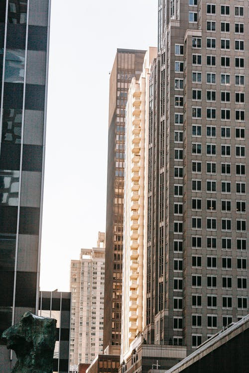 Modern multistory building facades under light sky in city