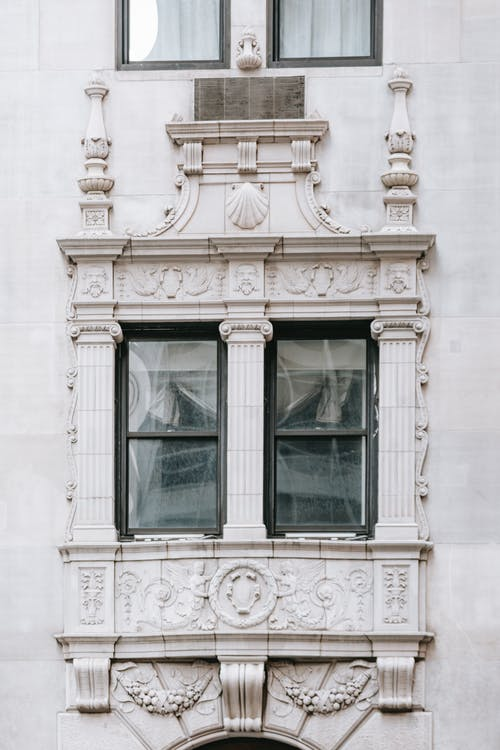 Old masonry house facade with windows between decorative columns on gray wall in city in daytime