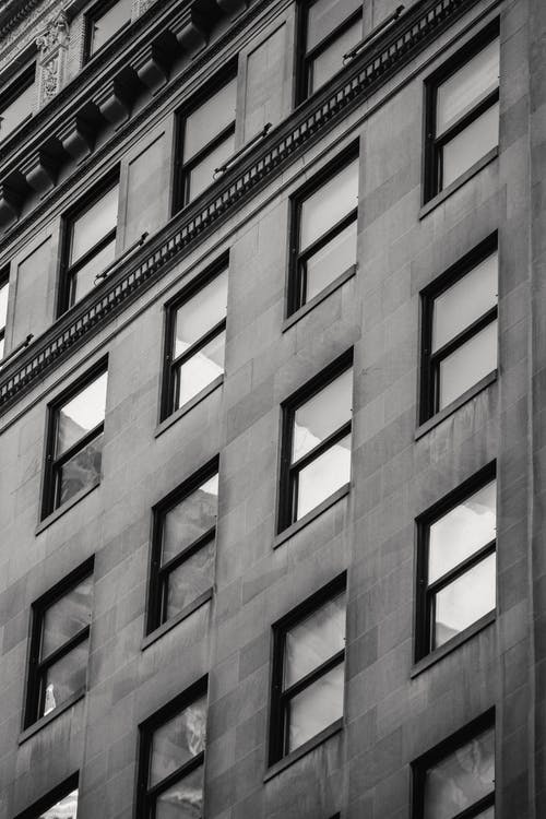 Black and white of multistory building exterior with decor and rectangular shaped windows in town