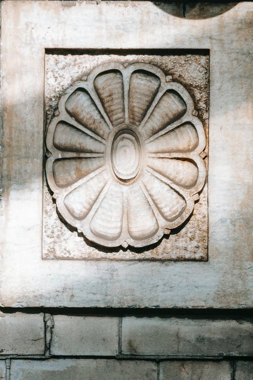 Floral ornament on shabby stone wall