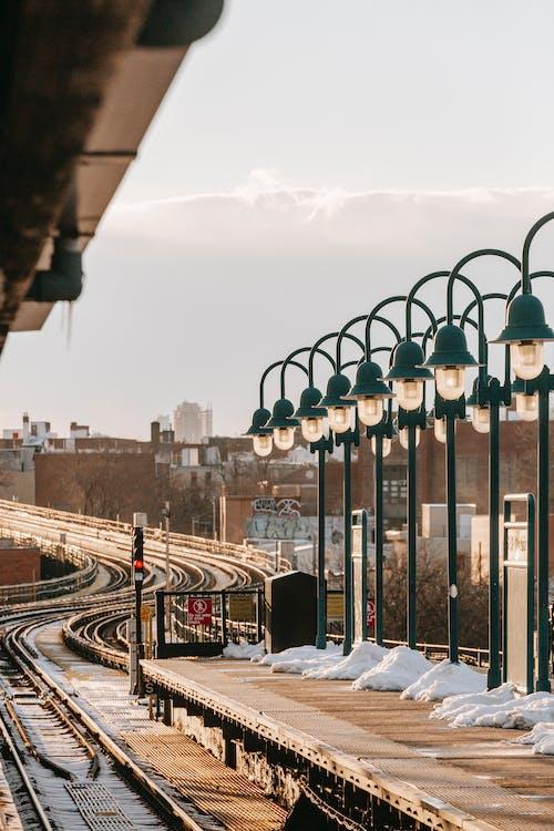 Streetlamps shining on railway platform in winter day