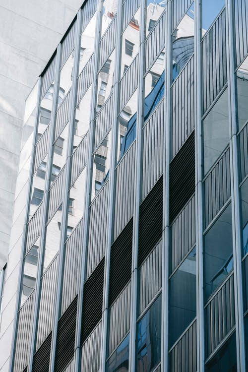 Exterior of modern multistory house with windows with reflections of buildings located on street in financial district of contemporary city