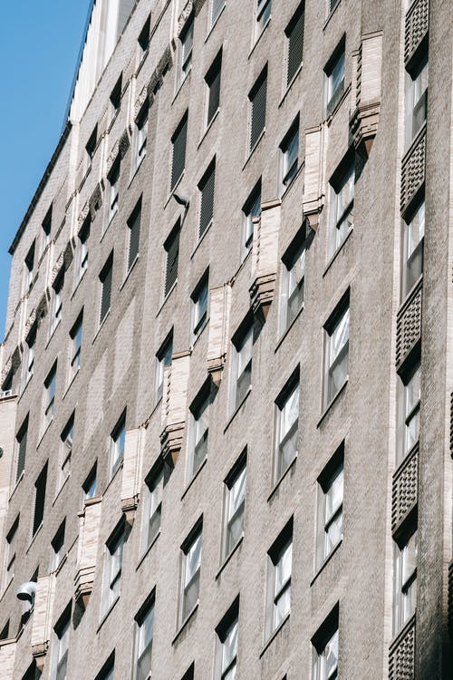 From below of concrete apartment building with many windows and balconies under blue sky