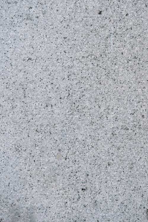Textured background of rough uneven gray surface with irregular black and white dots