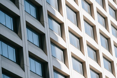 Low angle of rows of modern glass windows on facade of contemporary white multistory building reflecting sunlight