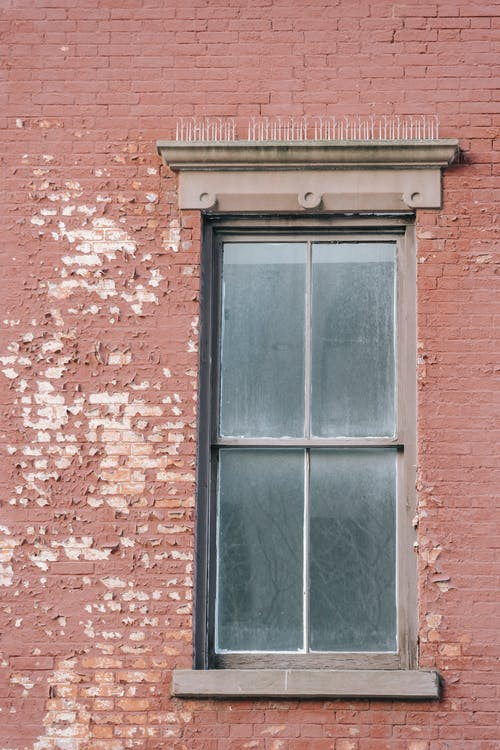 Dark unwashed window located on shabby red brick wall of old residential building