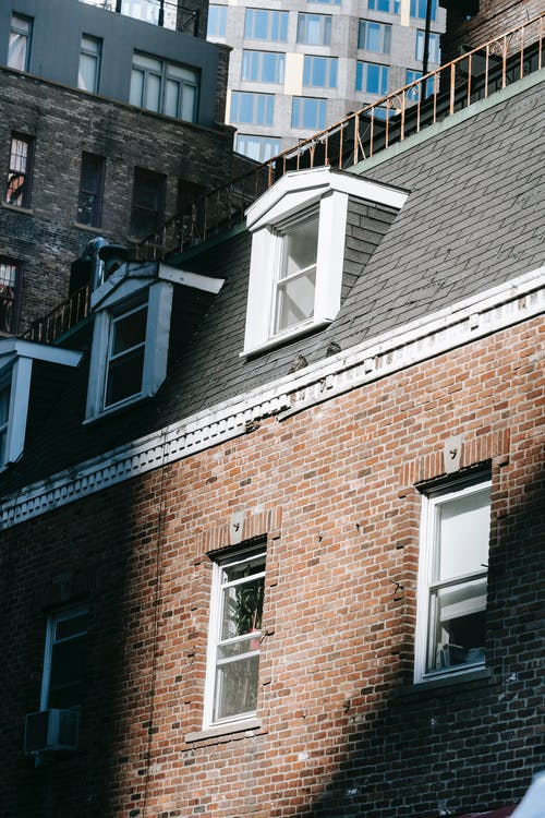 Cityscape with old brick building facade with windows and attic at roof in sunlight