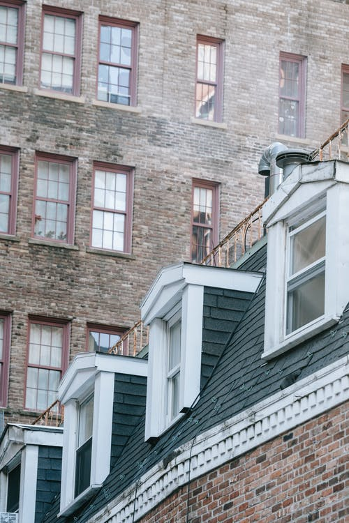 Rows of attic windows at roof against shabby facade of old brick building