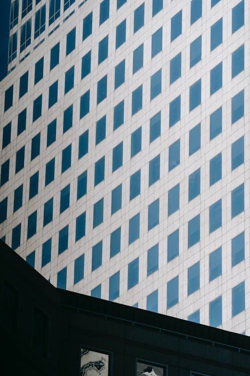 Low angle exterior design of contemporary urban high rise building with gray panels and geometric pattern of windows for architecture background
