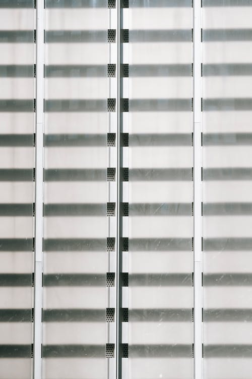 Geometric architecture background of exterior of transparent glass window closed with shutter stripes