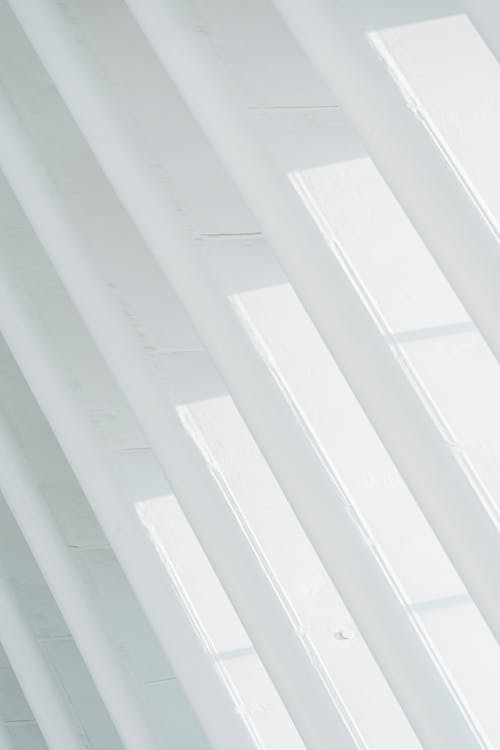 Architectural fragment of contemporary construction with white geometric ribbed wall in sunlight as minimalist style background