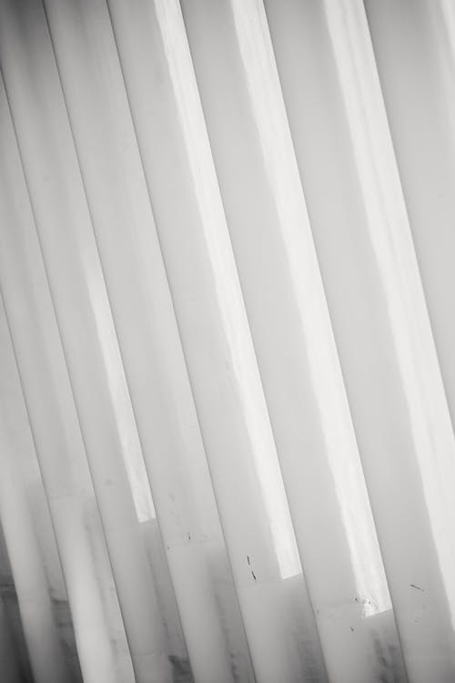 Textured background of white shutters on window