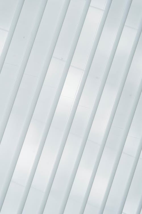 From below of symmetric white ribs and windows on walls of creative modern building in sunlight as abstract background