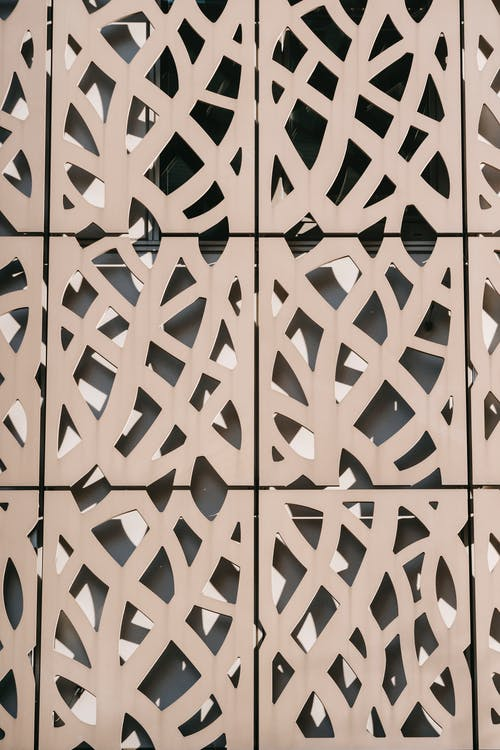 Abstract background of carved ornamental panel of modern building facade located in city on sunny day