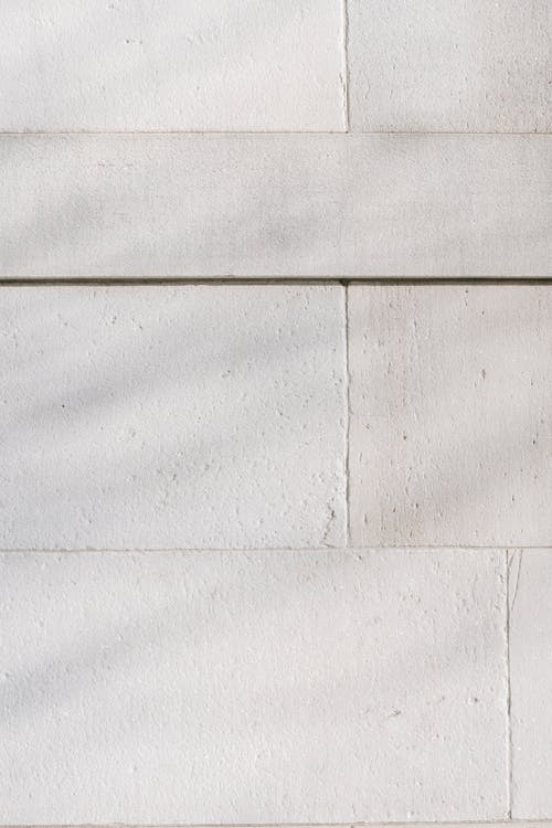 Abstract background of surface of textured white stone wall with scratches on sunny day