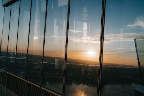 View through panoramic windows on coastal city and marina at observation deck at sundown