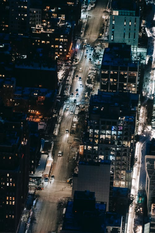 Drone view of road with cars riding between modern multistory buildings with glowing lights located on street of city at night time