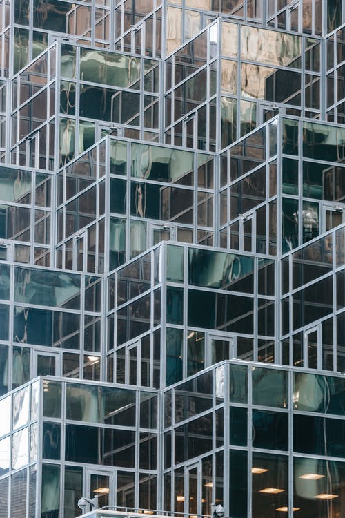 Full frame of contemporary financial skyscraper with geometric glass mirrored walls in daytime