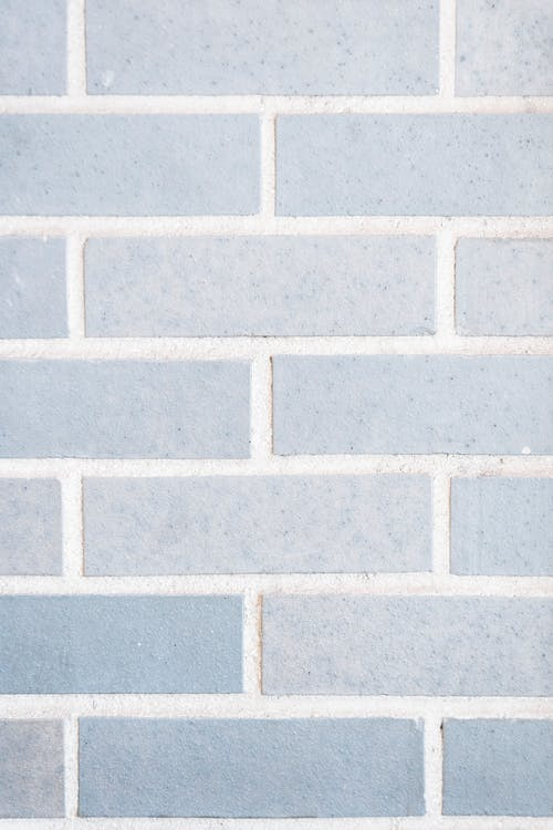 Full frame minimalist background of light gray wall with rows of bricks on wall