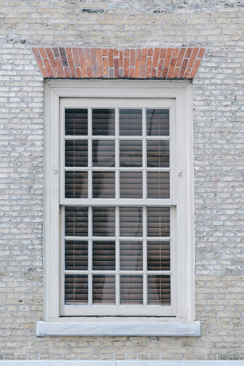 Facade of aged brick apartment building with window in wooden frame shut with blinds